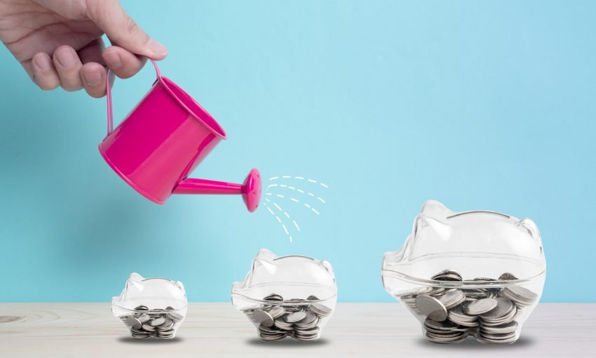 Transparent piggy bank filled with coins on wood background.Saving investment colorful concept.Watering can and money growth drawn concept for business investment, savings and making money.