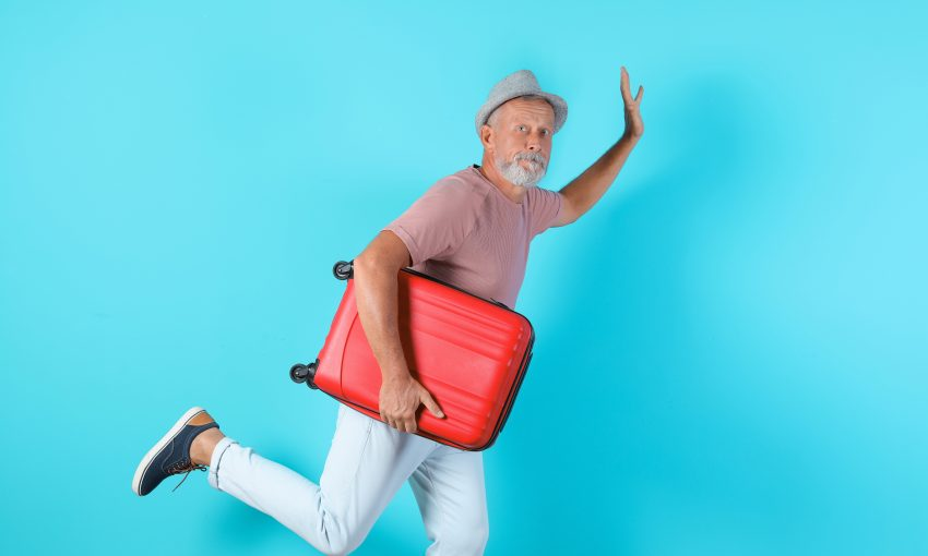 Senior man with suitcase running on color background. Vacation travel